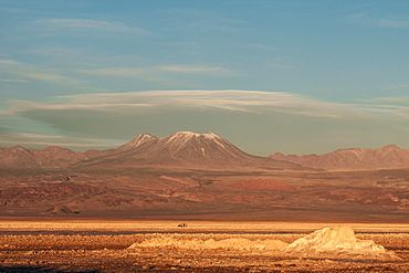 Hikers out on the Atacama Salt Flats, with snow-capped volcanic peak in the background, near San Pedro de Atacama, Chile, South America