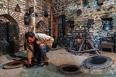 Sampling wine from underground vats, Nodari Wine Cellar, Velistsikhe, near Sighnaghi, Kakheti, Georgia, Central Asia, Asia