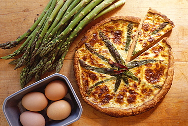 Overhead shot of asparagus quiche, a French vegetarian dish, with eggs and raw fresh asparagus
