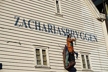 Statue of man holding fish, Bryggen, Bergen, Hordaland, Norway, Scandinavia, Europe