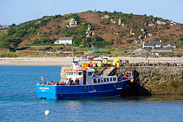 Travellers boarding boat at New Grimsby Quay on Tresco with Bryher in background, Isles of Scilly, England, United Kingdom, Europe