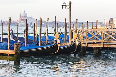 Gondals moored at waterfront, Riva degli Schiavoni, with view to San Giorgio Maggiore, Venice, UNESCO World Heritage Site, Veneto, Italy, Europe