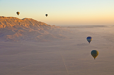 Hot air balloons on an excursion flying over the desert early morning at dawn , sunrise, on the West bank of the river Nile near Luxor, Egypt, North Africa, Africa