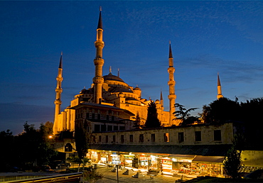Domes and minarets of the Blue Mosque (Sultan Ahmet Camii), and stalls of the Arasta Carsisi (the Cavalry Bazaar) selling carpets and souvenirs floodlit at night, Sultanahmet, central Istanbul, Turkey, Europe
