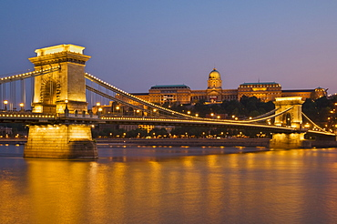 The Chain Bridge (Szechenyi Lanchid), over the River Danube, illuminated at sunset with the Hungarian National Gallery behind, UNESCO World Heritage Site, Budapest, Hungary, Europe