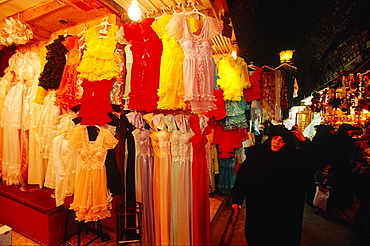 Syria, Aleppo, The Souks (Traditional Covered Markets), Veiled Woman Dressed In Black Passing Female Underwear Stall