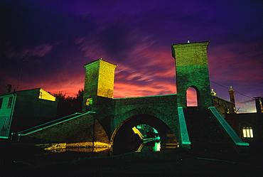 Italy, Emilia Romagna, River Po Delta, Comarchio, The Famous Bridge With Towers At Dusk