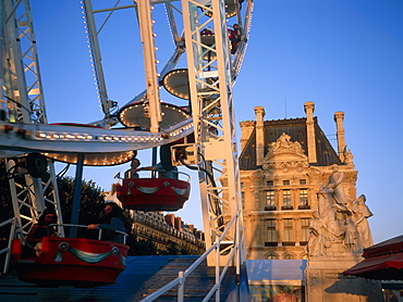 Merry-go-round and ferris wheel at dusk in the Tuileries Park, Paris, France, Europe