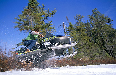 Snowmobile travelling at speed, Sunset Country, Ontario, Canada, North America