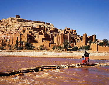 Morocco, Ouarzazate Region, Ait Ben Haddou Kasbah (Mud Fortress) At Spring, Fellah (Peasant) And Child Crossing The Oued (River)