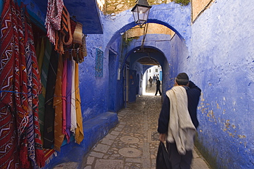 Man walking through pastel coloured streets of Chefchaouen, Morocco, North Africa, Africa