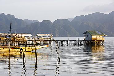 Unusual shaped coastal hills of Coron Island, and stilt houses, Coron Town, Busuanga Island, Palawan Province, Philippines, Southeast Asia, Asia