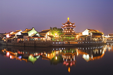 Traditional old riverside houses and pagoda illuminated at night in Shantang water town, Suzhou, Jiangsu Province, China, Asia