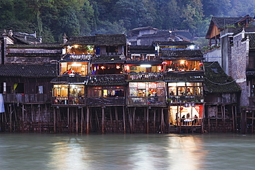 Wooden stilt houses on riverside, old town of Fenghuang, Hunan Province, China, Asia