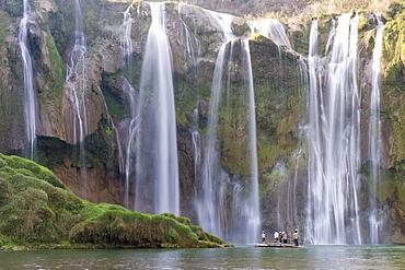 Tourists on a bamboo raft under Jiulong Falls (Nine Dragon waterfall), Luoping, Yunnan Province, China, Asia