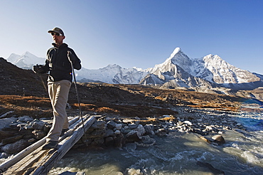 Trekker crossing a mountain stream, Ama Dablam, 6812m, Solu Khumbu Everest Region, Sagarmatha National Park, Himalayas, Nepal, Asia - 733-4244