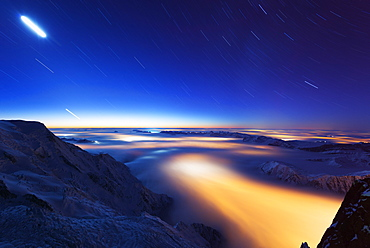 Sea of clouds weather inversion over Chamonix valley, star and moon light trails, Chamonix, Rhone Alpes, Haute Savoie, France, Europe