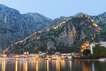 Venetian built fort with bastions highlighted by lights at twilight, Kotor, Montenegro, Europe