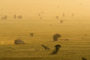 A safari vehicle driving across the plains of Tsavo at sunset, Kenya, East Africa, Africa