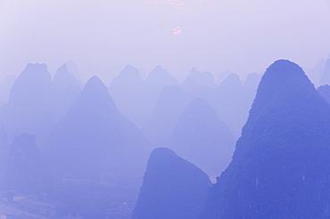 Karst landscape, haze and rising sun, Yangshuo, Guangxi Province, China, Asia