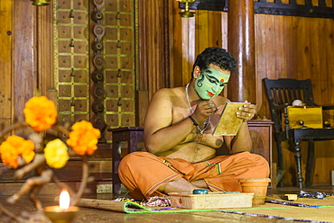 Man applying makeup for Kerala Kathakali performance in Kochi, Kerala, India, Asia