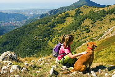 Girl and dog, looking at view of Camaiore and Tyrrhenian Sea from Apuan Alps (Alpi Apuane), Lucca Province, Tuscany, Italy, Europe