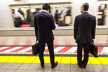 Two businessmen waiting for a train on the Tokyo Metro, Tokyo, Japan, Asia