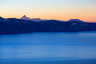 Dusk over the still waters of Crater Lake, the deepest lake in the U.S.A., with Mount Thielsen, part of the Cascade Range, Oregon, United States of America, North America