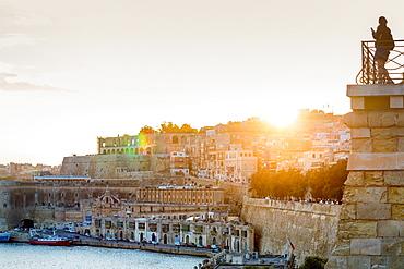 Person photographing the Grand Harbour in Valletta at dusk. Valletta, Malta, Mediterranean, Europe