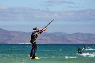 Man jumping whilst kiteboarding off the Playa de La Barca, Costa Calma, on the volcanic island of Fuerteventura, Canary Islands, Spain, Atlantic, Europe