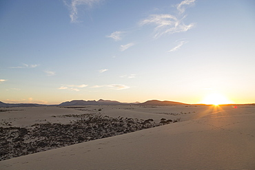The sun setting over the dramatic Dunas de Corralejo on the volcanic island of Fuerteventura with mountains beyond, Fuerteventura, Canary Islands, Spain, Europe