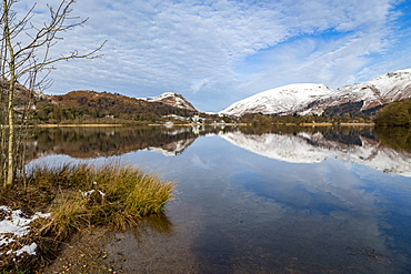 Shoreline and perfect reflection of snow covered mountains and sky in the still waters of Grasmere, Lake District National Park, UNESCO World Heritage Site, Cumbria, England, United Kingdom, Europe