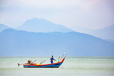 Fisherman on small boat, Strait of Malacca with Thai island of Ko Tarutao from Datai Bay Beach (Pantai Teluk Datai), Andaman Sea, Malaysia, Southeast Asia, Asia