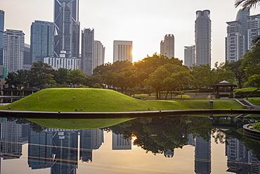 Kuala Lumpur skyline reflected in a still pond in KLCC Park at sunrise, Kuala Lumpur, Malaysia, Southeast Asia, Asia
