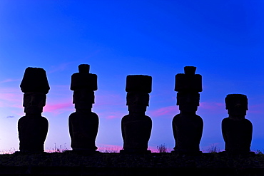Anakena beach, monolithic giant stone Moai statues of Ahu Nau Nau, four of which have topknots, silhouetted at dusk, Rapa Nui (Easter Island), UNESCO World Heritage Site, Chile, South America