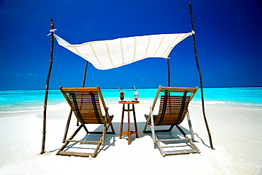 Two deck chairs under shelter on beach, Maldives, Indian Ocean, Asia