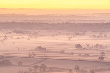 Dawn over the mist shrouded countryside of the Somerset Levels in winter, Glastonbury, Somerset, England, United Kingdom, Europe
