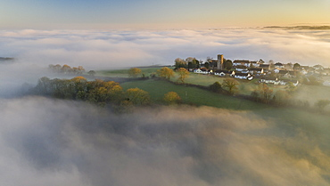 Aerial view by drone of rural village in evening light in winter, surrounded by fog, Coldridge, Devon, England, United Kingdom, Europe
