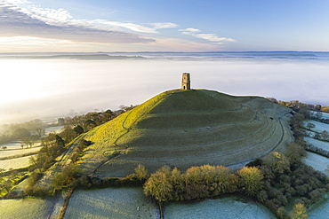 View by drone of St. Michael's Tower on Glastonbury Tor at dawn in winter, Somerset, England, United Kingdom, Europe