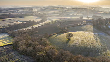 Aerial vista by drone of frosty rolling countryside at dawn in spring, Devon, England, United Kingdom, Europe