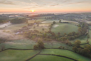 Misty sunrise over rolling countryside, South Tawton, Devon, England. Spring (May) 2020.