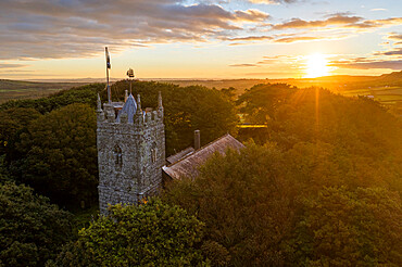St Dennis Parish Church emerging from trees at sunrise, St Dennis, Cornwall, England. Autumn (August) 2020.
