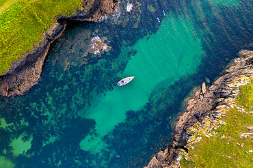 Aerial view of a yacht moored in Port Quin, Cornwall, England. Autumn (September) 2020.