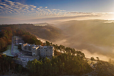 Aerial vista of Castle Drogo and the Teign Valley in morning mist, Dartmoor, Devon, England. Winter (November) 2020.