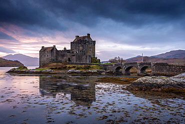 Sunset behind Eilean Donan Castle on Loch Duich in the Scottish Highlands, Scotland, UK.