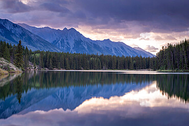 Sunrise over the mountains of the Rockies, reflected in Johnson Lake, Banff National Park, Alberta, Canada.