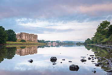 Carew Castle reflected in the mill pond at dawn, Pembrokeshire, Wales, United Kingdom, Europe