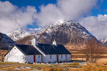 Black Rock Cottage bothy on Rannoch Moor with a snow dusted Buachaille Etive Mor looming behind in winter, Highlands, Scotland, United Kingdom, Europe
