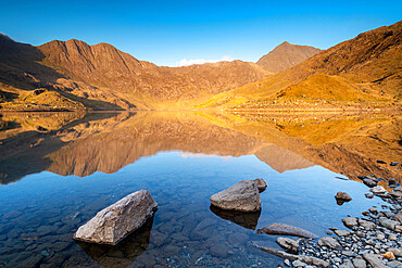 Early morning sunlight on Snowdon in spring, reflected in Llyn Llydaw, Snowdonia National Park, Wales, United Kingdom, Europe