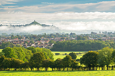View across the town of Street towards Glastonbury Tor on a misty autumn morning, Somerset, England, United Kingdom, Europe